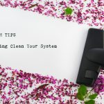 A vacuum cleaner head clearing a path through pink and purple flower petals, with the text: Tech Tips: Spring Clean Your System